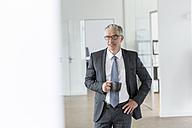 Mature businessman standing in office, holding cup of coffee - FMKF04144