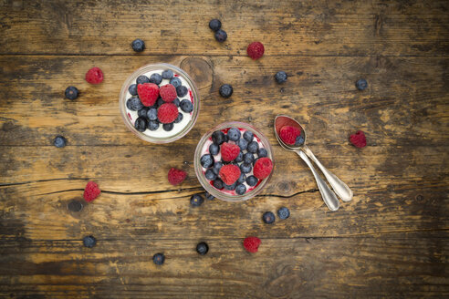 Two glasses of Greek yogurt with berry groats, fresh blueberries and raspberries on wood - LVF06116