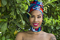 Portrait of smiling young woman with piercings wearing traditional Brazilian headgear - ABZF02018