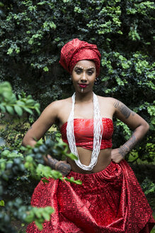 Portrait of young woman with piercings and tatoos wearing traditional Brazilian clothing - ABZF02021