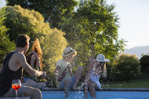 Four friends having fun at the pool edge in the garden - ZOCF00345