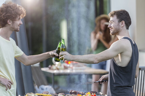 Two men clinking beer bottles at barbecue grill - ZOCF00354
