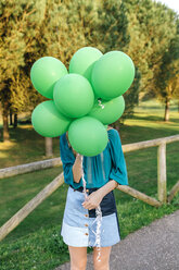 Young woman hiding behind green balloons - DAPF00755