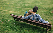 Back view of young couple sitting on bench on a meadow - DAPF00761