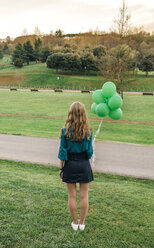 Back view of young woman with   green balloons standing on a meadow - DAPF00764
