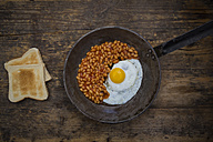 Fried egg and baked beans in frying pan on wood - LVF06123
