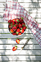 Bowl of strawberries, knife and kitchen towel on garden table - LVF06128