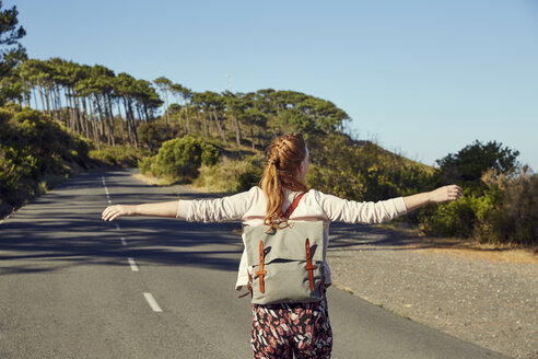 South Africa, Cape Town, Signal Hill, happy young woman with outstretched arms on country road - SRYF00517