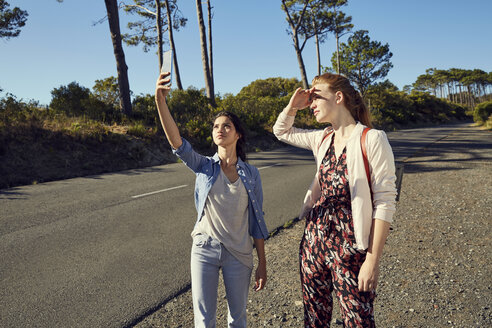 South Africa, Cape Town, Signal Hill, two young women with cell phone on a trip - SRYF00529