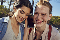 Two smiling young women sharing cell phone outdoors - SRYF00532