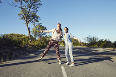 South Africa, Cape Town, Signal Hill, two happy young women on country road - SRYF00535