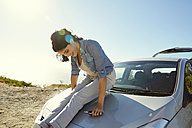 Happy young woman sitting on a car - SRYF00538