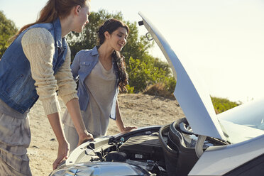 Two young women checking their car standing at the roadside - SRYF00541