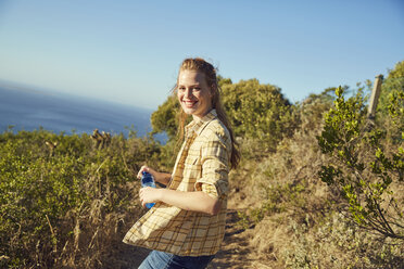 South Africa, Cape Town, Signal Hill, smiling young woman hiking at the coast - SRYF00559