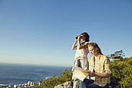 South Africa, Cape Town, Signal Hill, two young women with map and binoculars overlooking the sea - SRYF00562