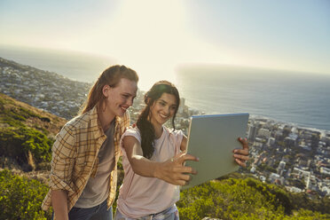 South Africa, Cape Town, Signal Hill, two young women above the city taking a selfie with tablet - SRYF00565