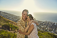 South Africa, Cape Town, Signal Hill, portrait of two young women hugging above the city - SRYF00568