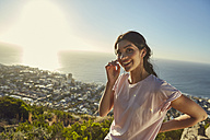 South Africa, Cape Town, Signal Hill, portrait of smiling young woman above the city - SRYF00571