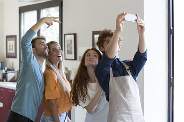Friends taking selfies in kitchen - ZOCF00363