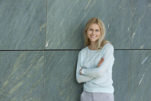 Portrait of smiling blond woman leaning against wall - CHAF01875