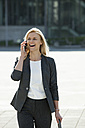 Portrait of laughing blond businesswoman on the phone - CHAF01878