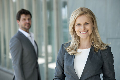 Portrait of smiling businesswoman with her partner watching in the background - CHAF01881
