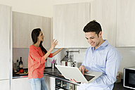 Smiling young man with woman in kitchen using laptop - FMOF00280