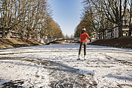 Woman ice skating on canal - MFF03510