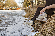 Close-up of woman putting on ice skates at canal - MFF03513
