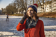 Ice skating woman listening to music with earphones - MFF03516