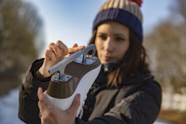 Woman examining the blade of her ice skate - MFF03519