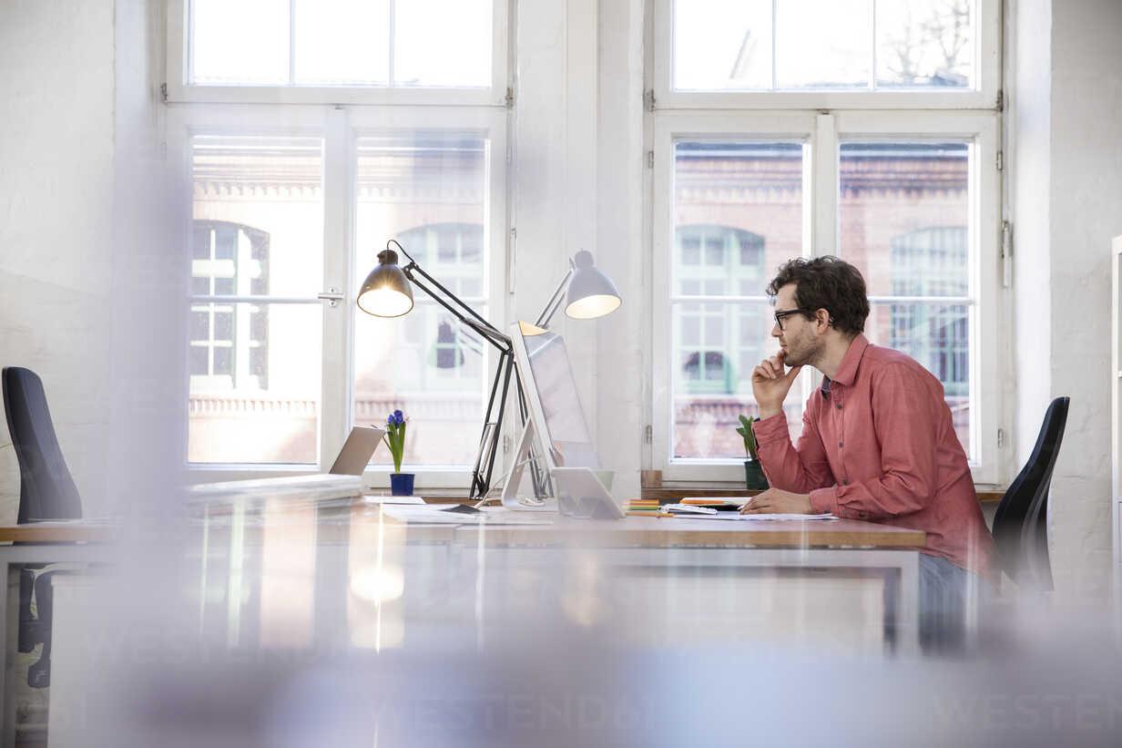 Man sitting at desk in office - FKF02255 - Florian Küttler/Westend61