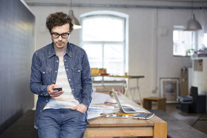 Man using cell phone in office - FKF02264