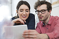 Man and woman looking at tablet in office - FKF02267
