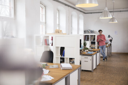 Man using cell phone in office - FKF02270