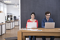 Man and woman using laptops on table in office - FKF02282