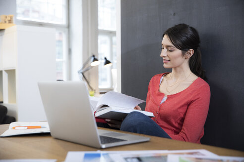 Woman with book and laptop at desk in office - FKF02285