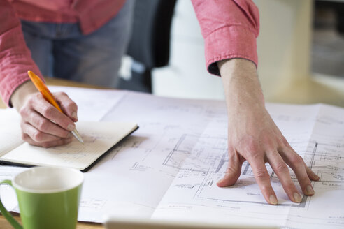 Close-up of man working on blueprint at desk in office - FKF02306