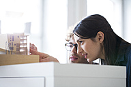 Man and woman discussing architectural model in office - FKF02318