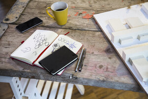 Notebook, smartphone, architectural model and coffee cup in modern informal office - FKF02321