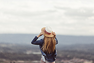Back view of redheaded woman wearing hat looking at distance - JPF00204