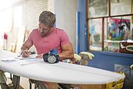 Surfboard shaper workshop, surfshop employee filling out paper work - ZEF13670