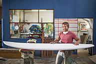 Surfboard shaper workshop, portrait of smiling surfshop employee with surfboard - ZEF13673