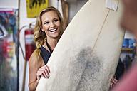 Surfboard shaper workshop, female employee smiling with surfboard - ZEF13688