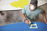 Surfboard shaper workshop, surfshop employee wearing dust mask - ZEF13694