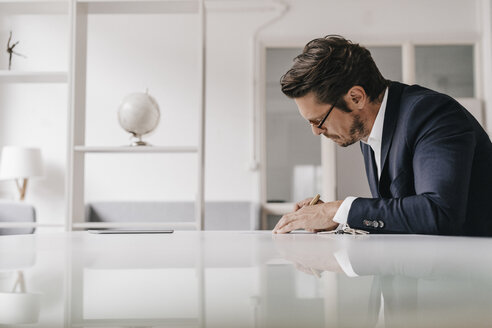 Businessman at table writing in notebook - KNSF01256