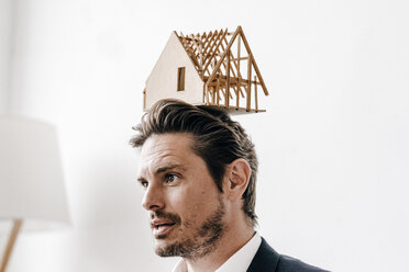 Man balancing an architectural model on his head - KNSF01283