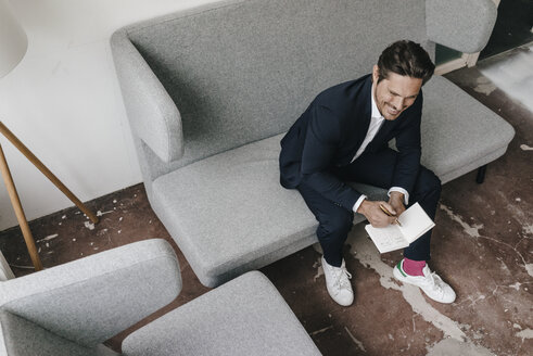 Smiling businessman with notebook on couch - KNSF01286