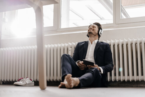 Businessman with tablet and headphones sitting on floor - KNSF01289