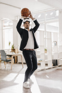 Businessman wearing VR glasses playing basketball in office - KNSF01292